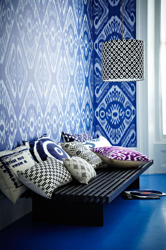 Background blue Ikat Bukhara motif pattern graphic print wallpaper, living room, balck wood slatted bench, assorted cushions, drum lampshade L etc 04/2011 pub orig